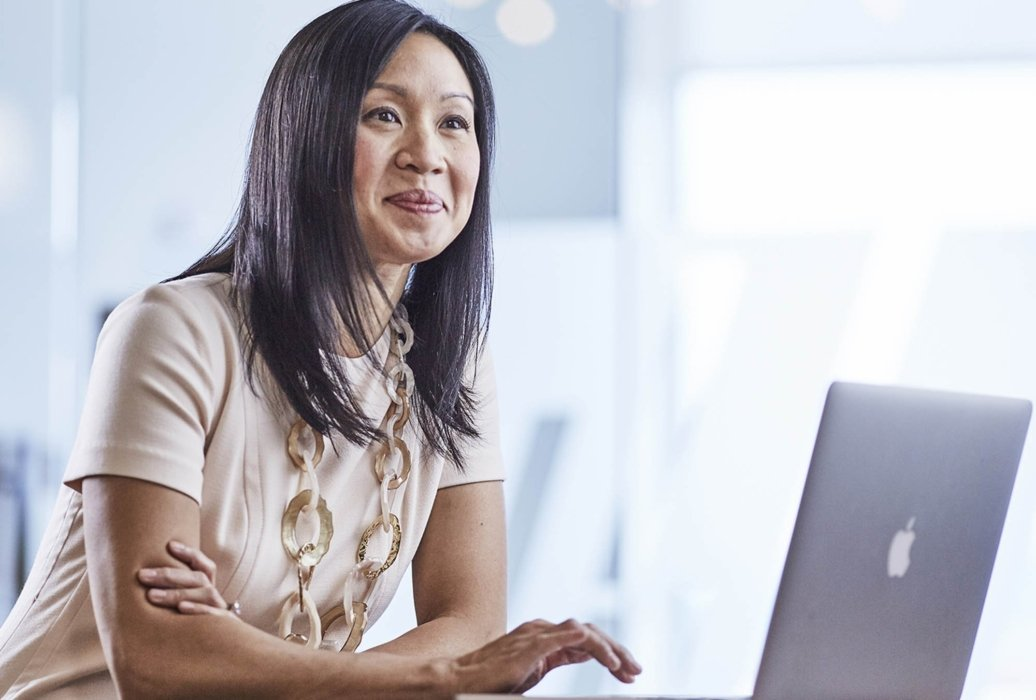 A woman in a corporate workplace office on a laptop