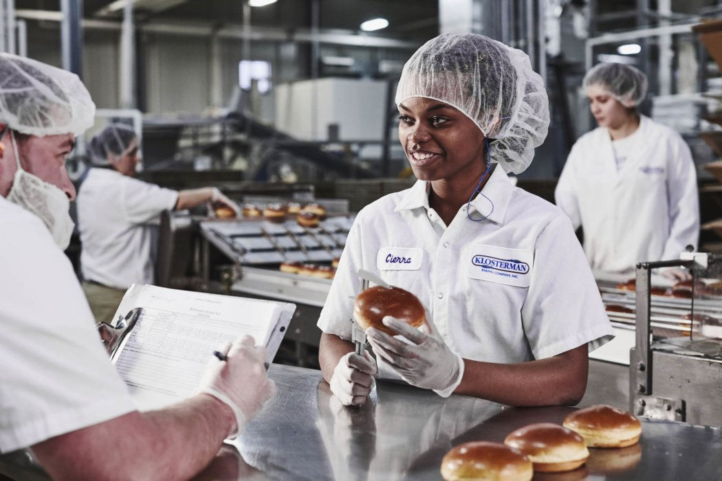 A worker in an industrial bakery inspecting buns with other workers