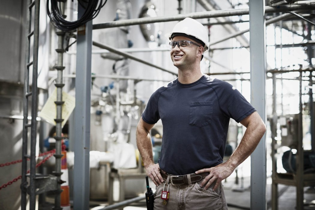 A man smiling wearing a hard hat in an industrial workplace