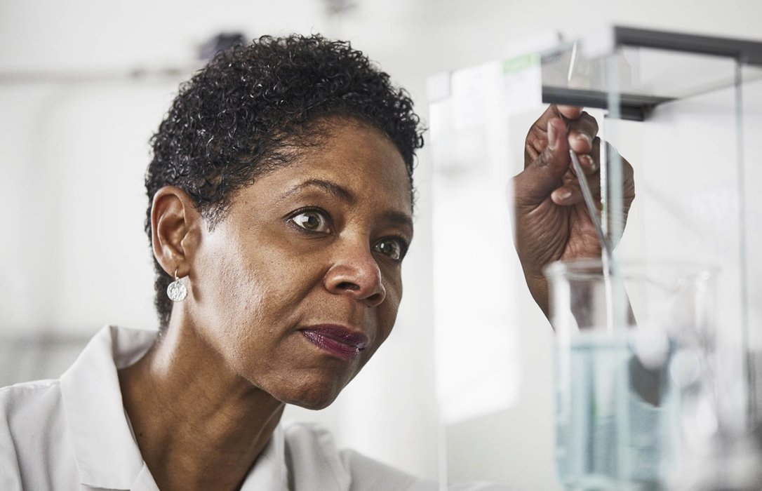 A female lab worker inspecting a beaker filled with pale blue liquid