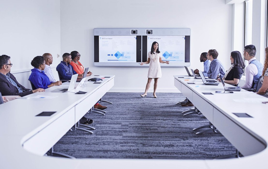 A woman in a corporate office workplace giving a presentation to a large group of people