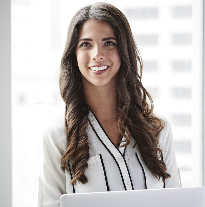 A portrait of a young woman in a corporate office setting
