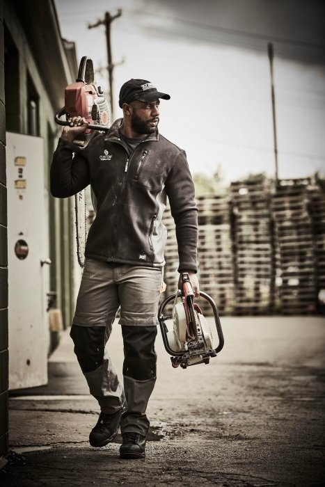 A man carrying power tools wearing work apparel - work photography