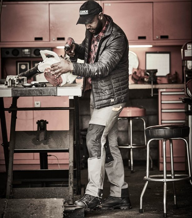 A man repairing a leaf blower with tools - - work photography