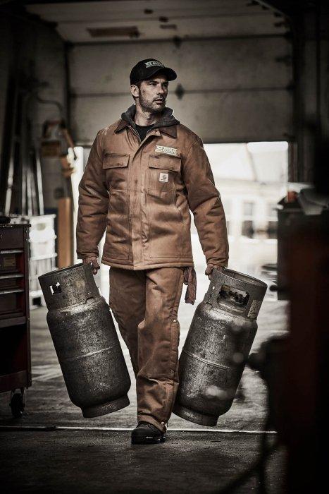 A man wearing carhartt work apparel carrying propane tanks - work photography