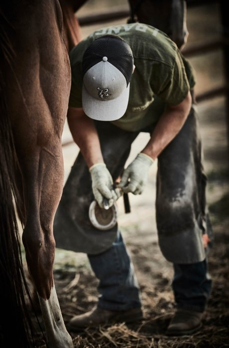 A man working on horse shoes wearing a rural cloth hat A man riding a horse wearing rural cloth apparel - work apparel photography