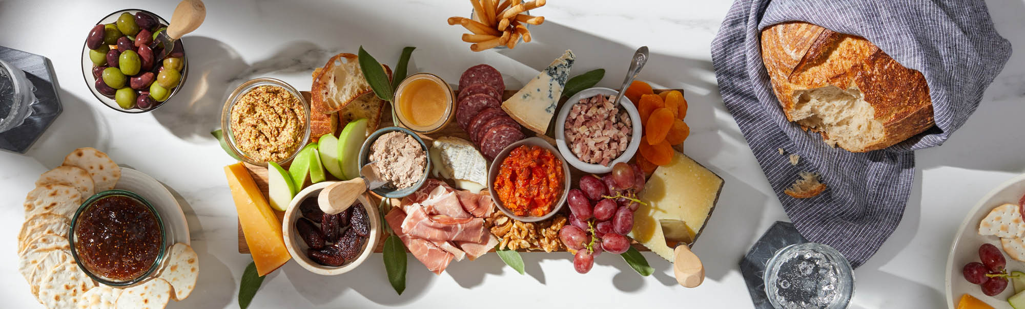 A full charcutiere board with meats fruits breads crackers and more - modern food photography