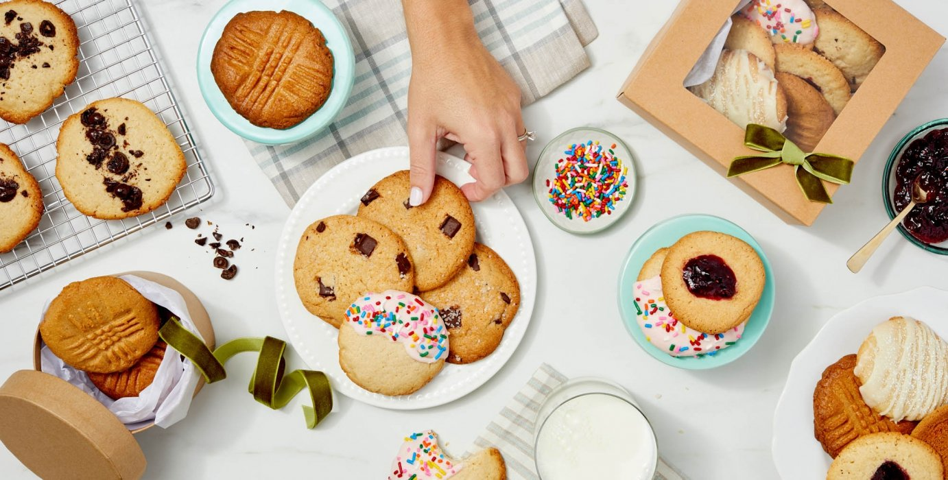 A had grabbing a tasty chocolate chip cookie from a table of cookies - food photography