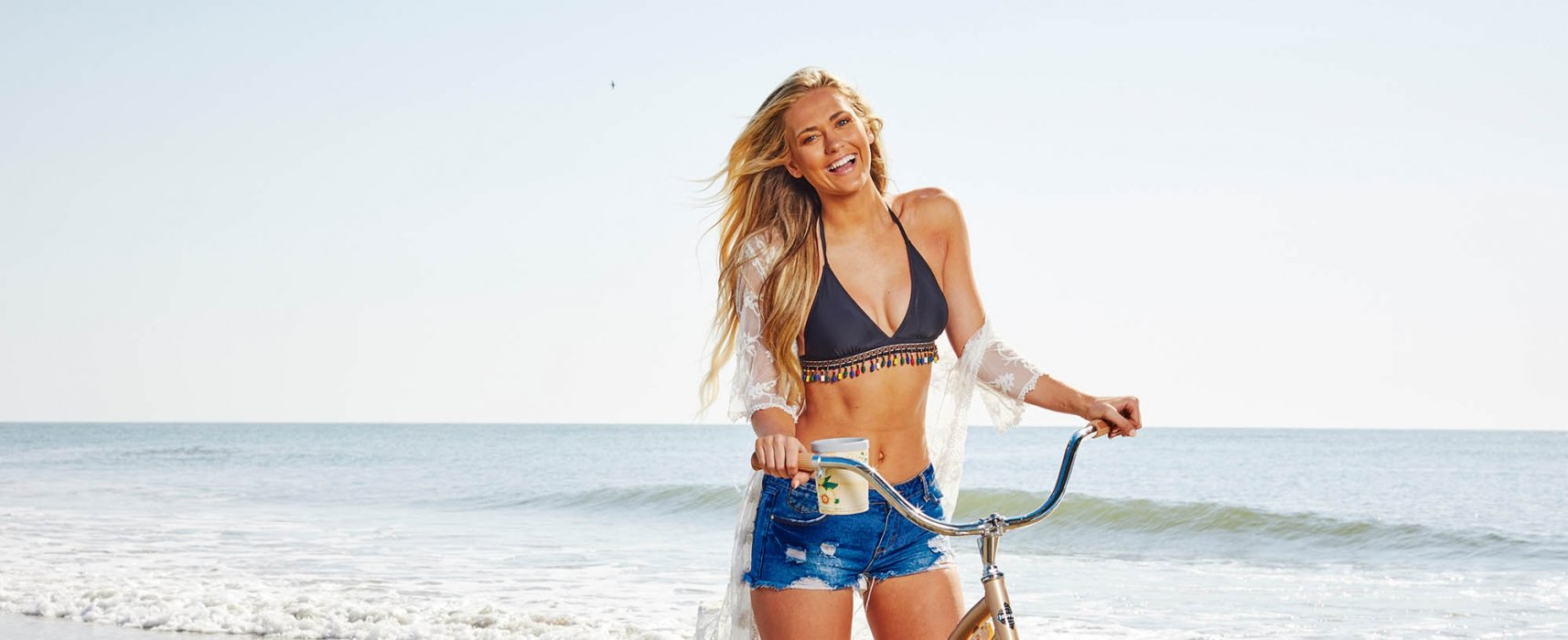 A young woman laughing with her bike on a beach - lifestyle photography