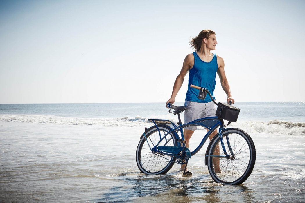 A young man walking his bike through the surf on a beach - lifestyle photography