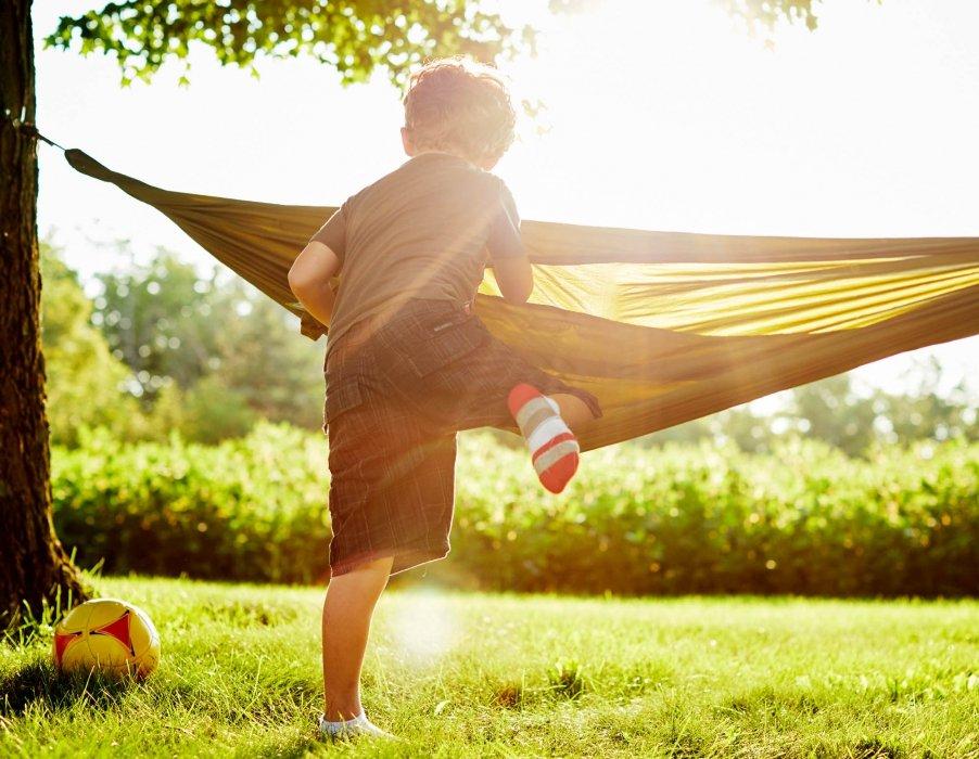 A young boy climbing into a hammock - lifestyle photography