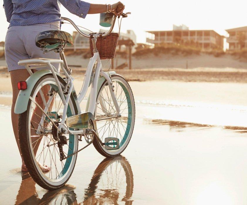 A woman on a beach walking their bikes - lifestyle photography