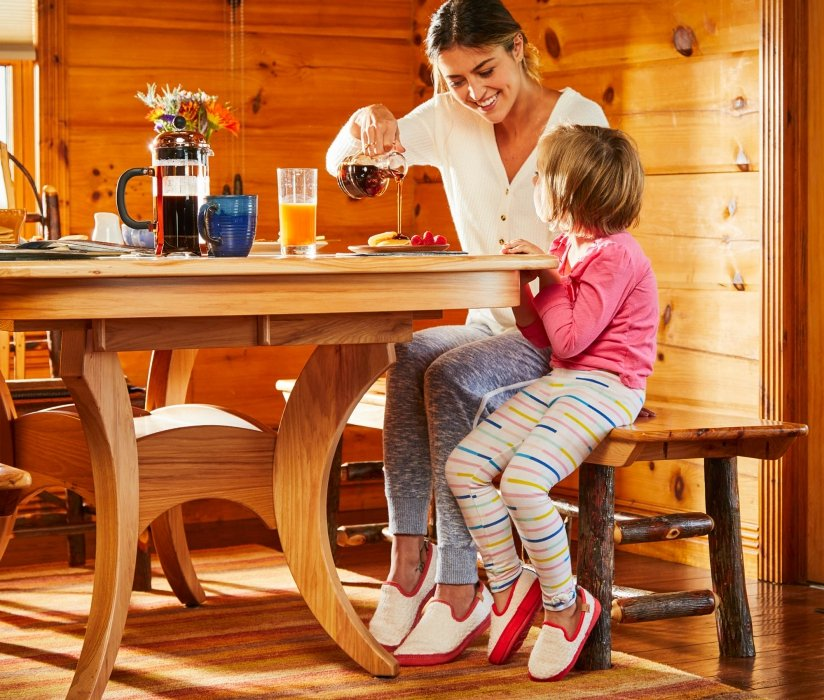A woman and young girl at breakfast in a wood house - lifestyle photography