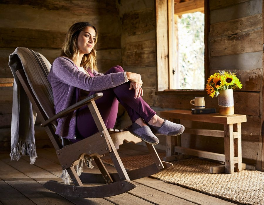 A young woman sitting in a rocking chair in log cabin - lifestyle photography