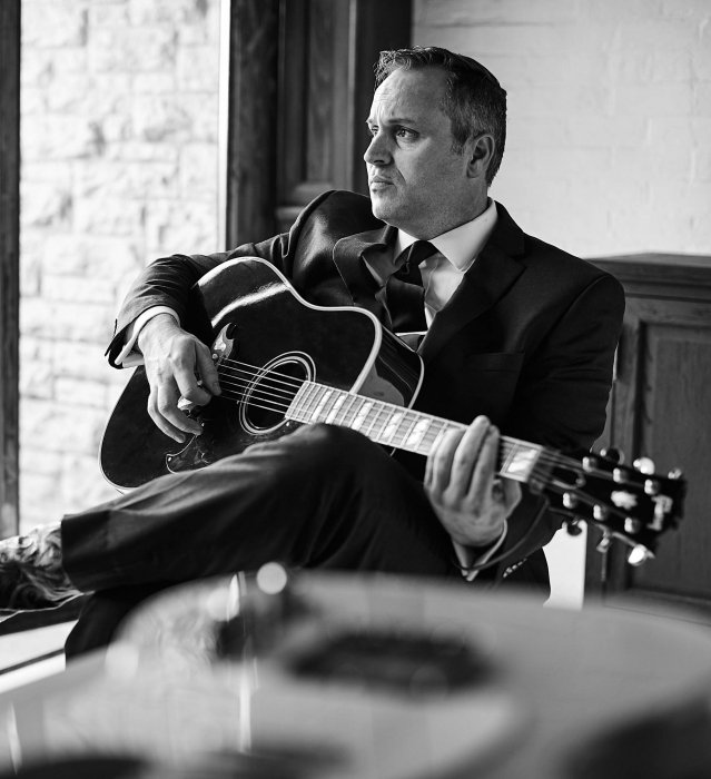 Portrait photography of a musician with black Gibson guitar