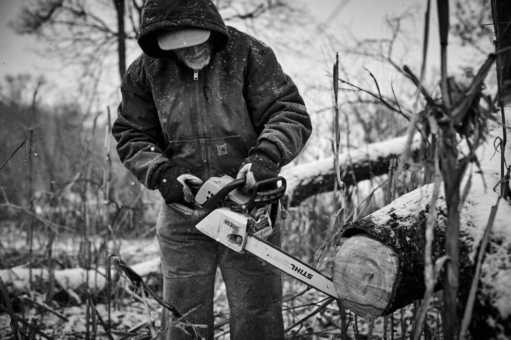 An old man working on a farm in winter with chain saw - lifestyle photography
