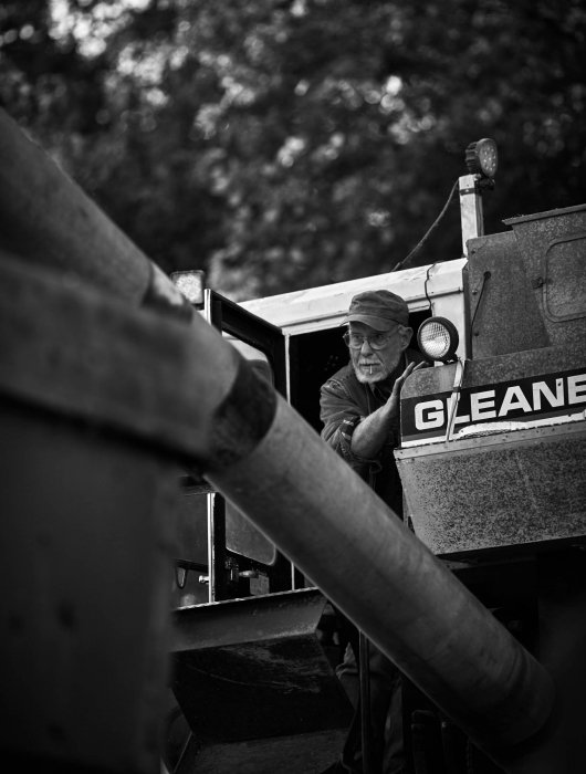 An old man looking out from farm machinery - lifestyle photography