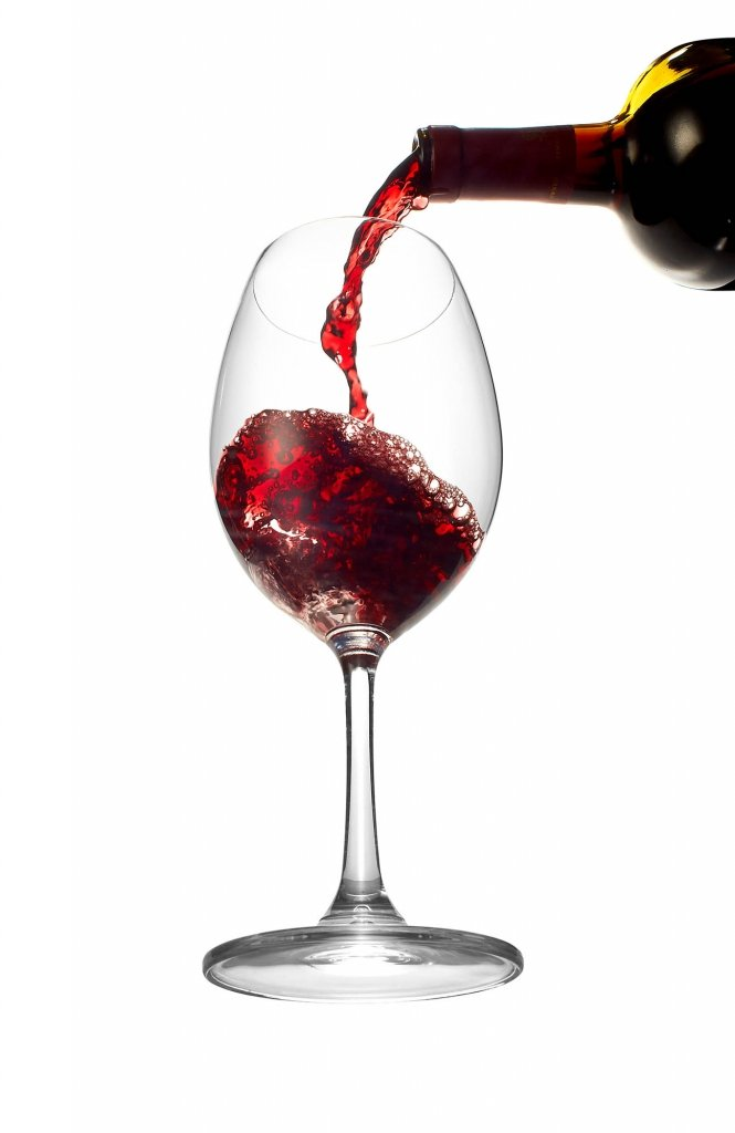 A glass of wine pouring into a glass - drink photography