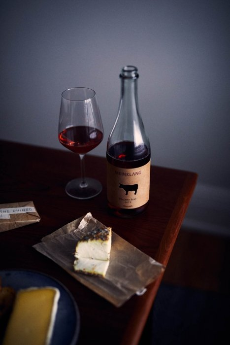 A darkly lit cheese spread with fine wine - wine photography