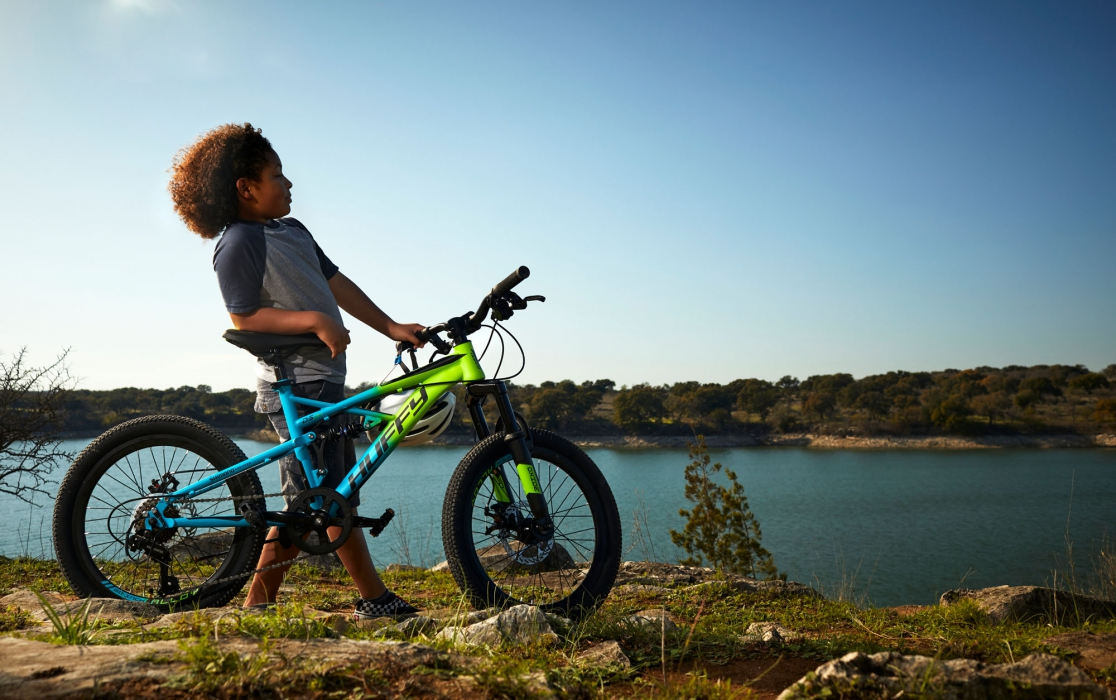 Young boy with huffy bike by a lake looking cool - product lifestyle photography