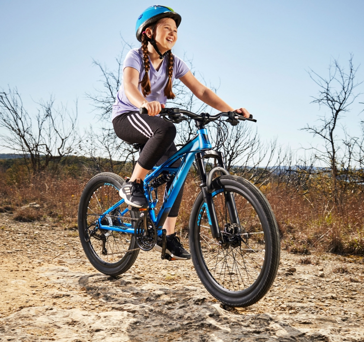 Young girl with huffy bike by a arid landscape - product lifestyle photography