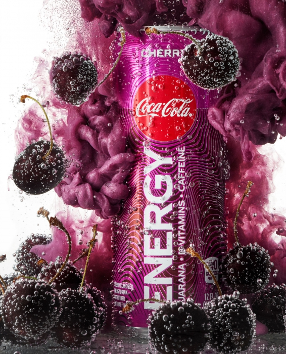 Cherry coca cola energy drink with plumes of purple and floating bubble covered cherries - drink photography