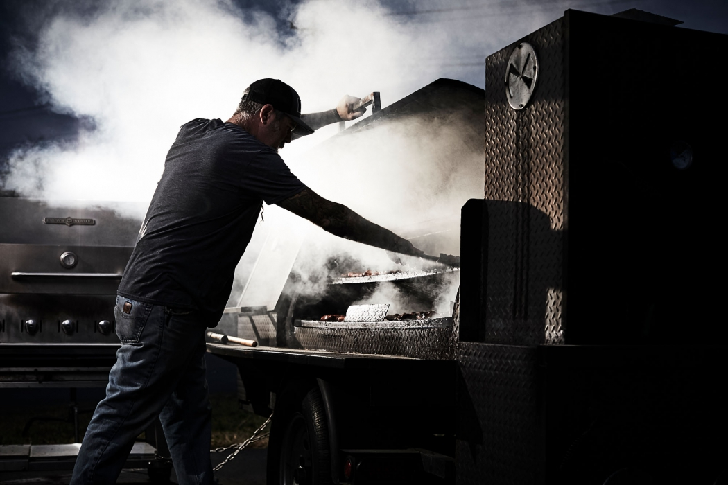 A man working on a smoker outside a restaurant - food photography