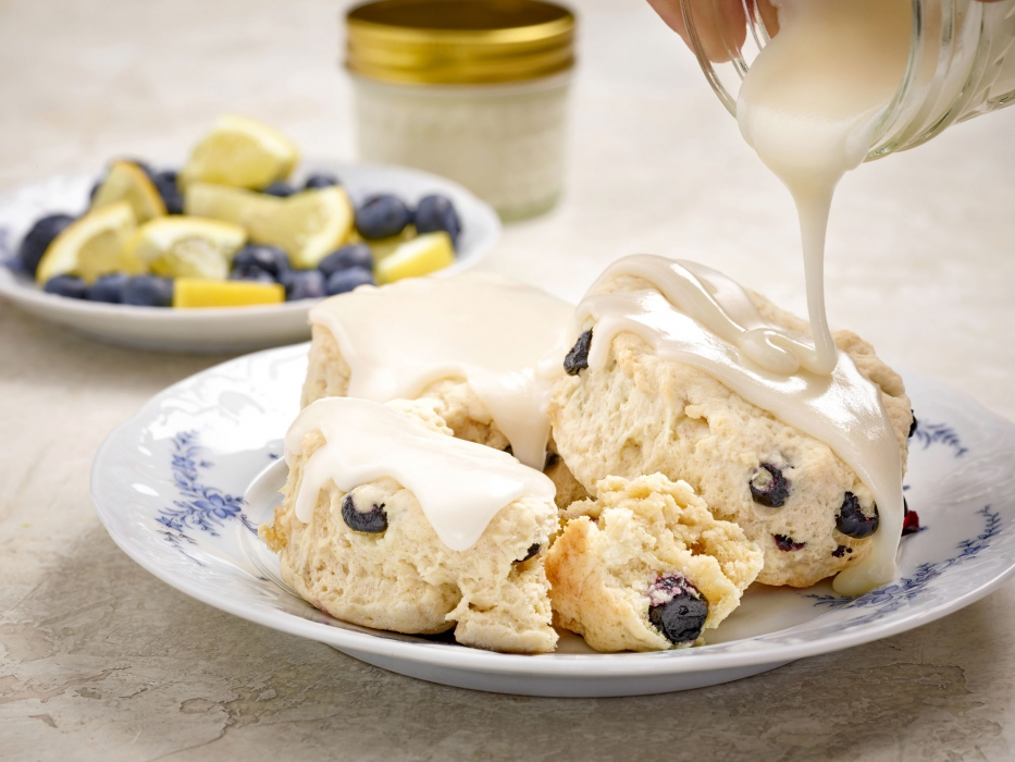 A delicious plate of blueberry lemon biscuits getting covered in white frosting - food photography