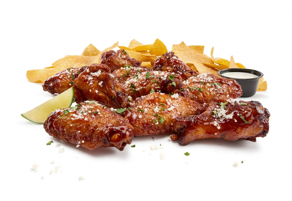 A clean shot of chicken wings and chips with sauce - food photography