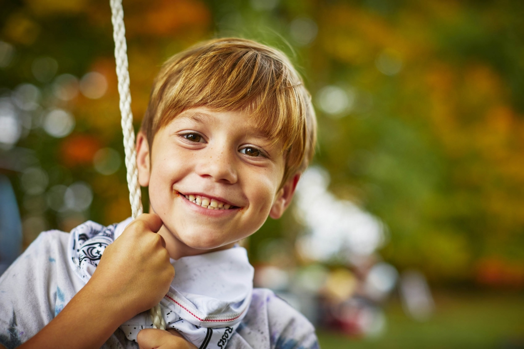 A young boy swinging and smiling on a rope swing in fall - lifestyle photography