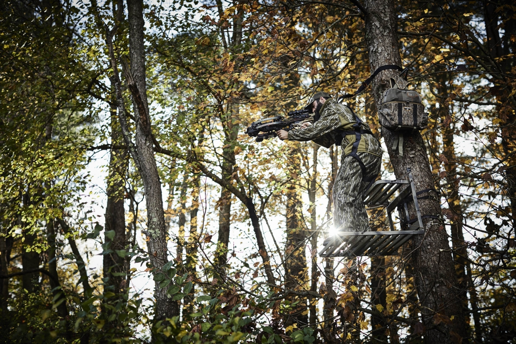 A hunter in a tree stand in forest with cross bow and bag