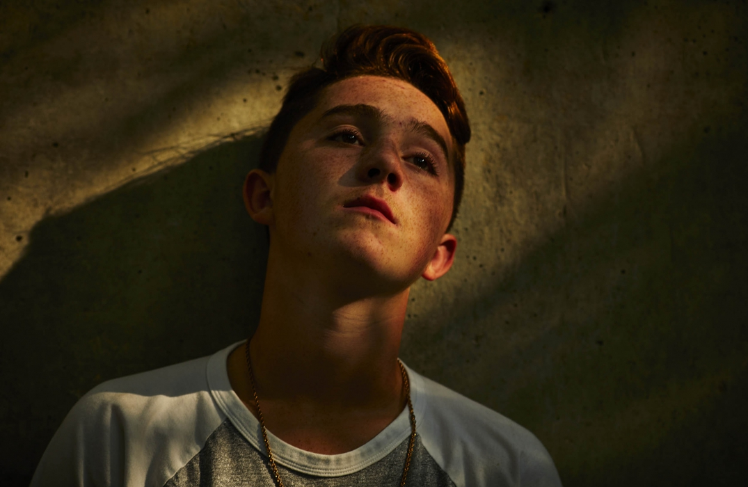 Portrait of a young man against a wall with some moody lighting - portrait photography