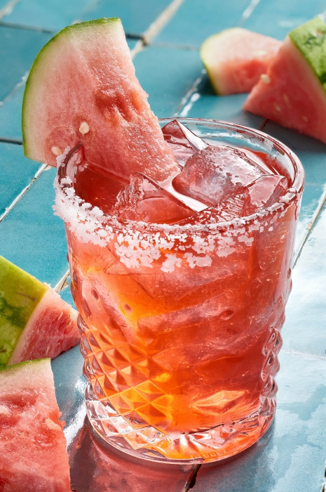 A wedge of watermelon on a watermelon margarita with salt - drink photography