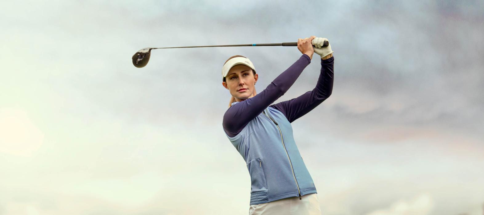 A woman golfing wearing KJUS apparel - lifestyle photography