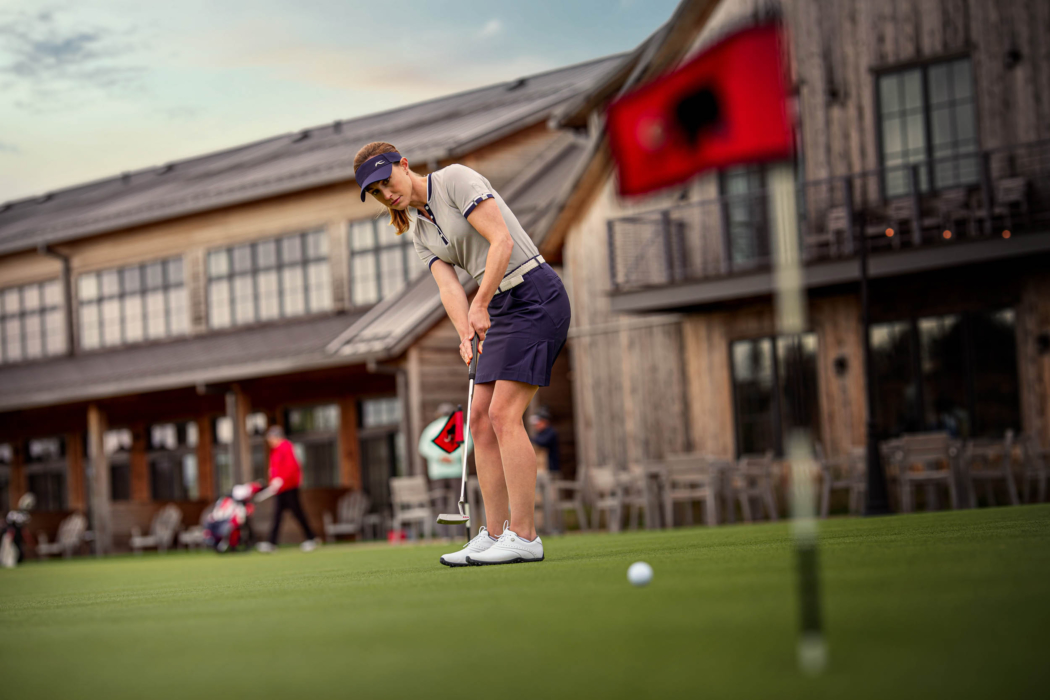 A woman golfing wearing KJUS apparel on the green - lifestyle photography