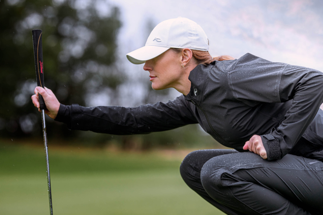 A woman wearing KJUS golf apparel in the rain - lifestyle photography