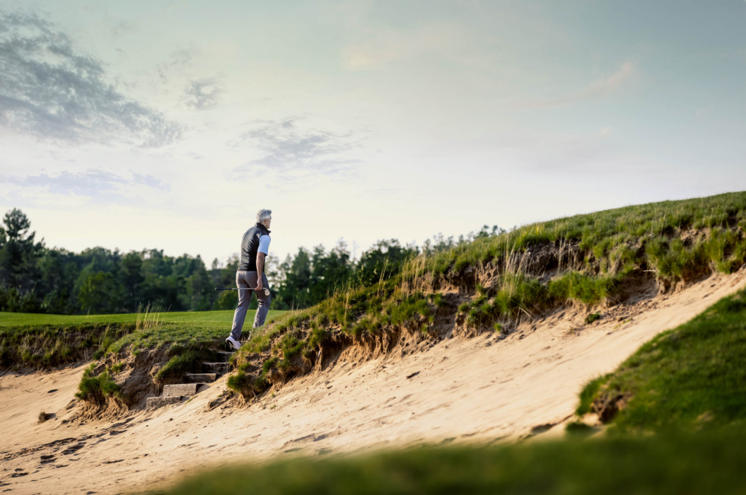 A man wearing KJUS golf apparel leaving a sand trap - lifestyle photography
