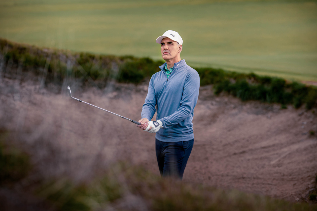 A man wearing KJUS golf apparel after a swing in a sand trap - lifestyle photography