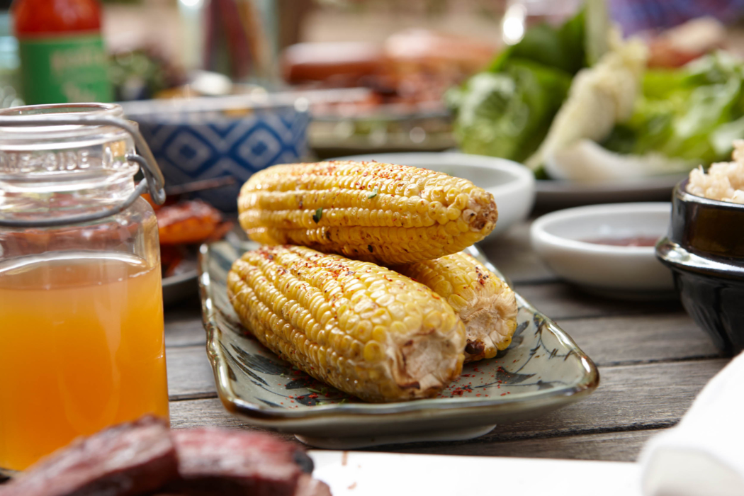 A table of food at a Korean BBQ with grilled corn - food photography