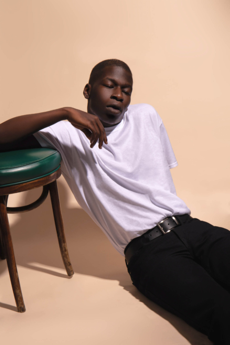 A man sitting on the floor leaning against a chair - modern photography - portrait photographer