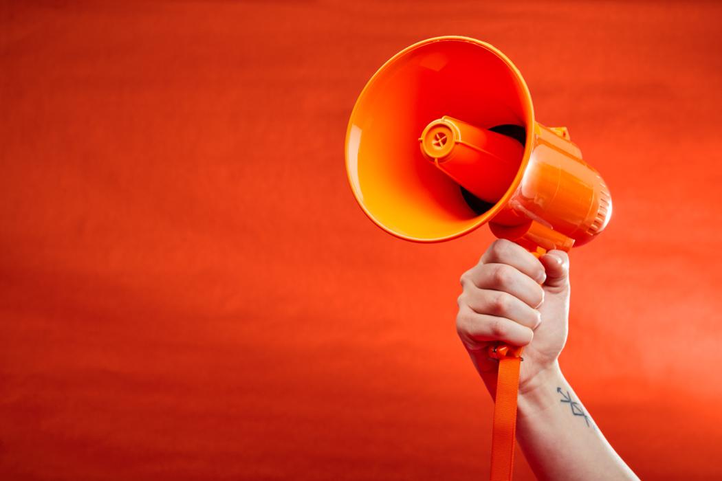 Website banner photo of orange megaphone on orange background