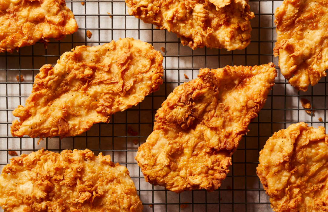 Food photography of fried chicken breasts on a drying rack