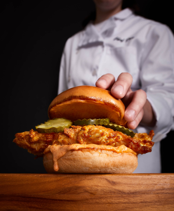 Food photography of chef placing the top bun on a nice fried chicken sandwich