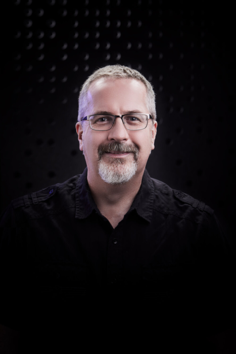 Portrait of a man with glasses and a beard on a modern dark background - portrait photography